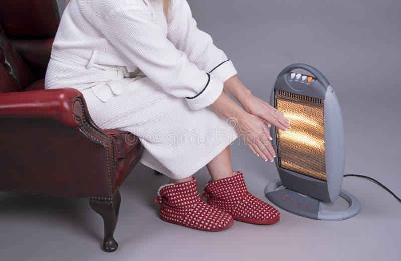Женщина греет ее руки на электрическом огне стоковые фотографии rf