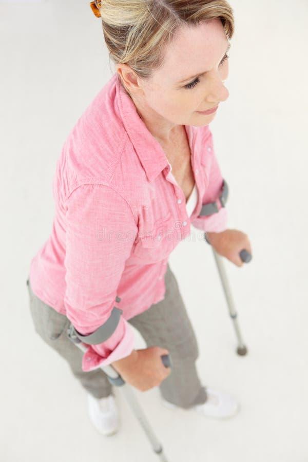 Женщина гуляя с костылями стоковые изображения rf