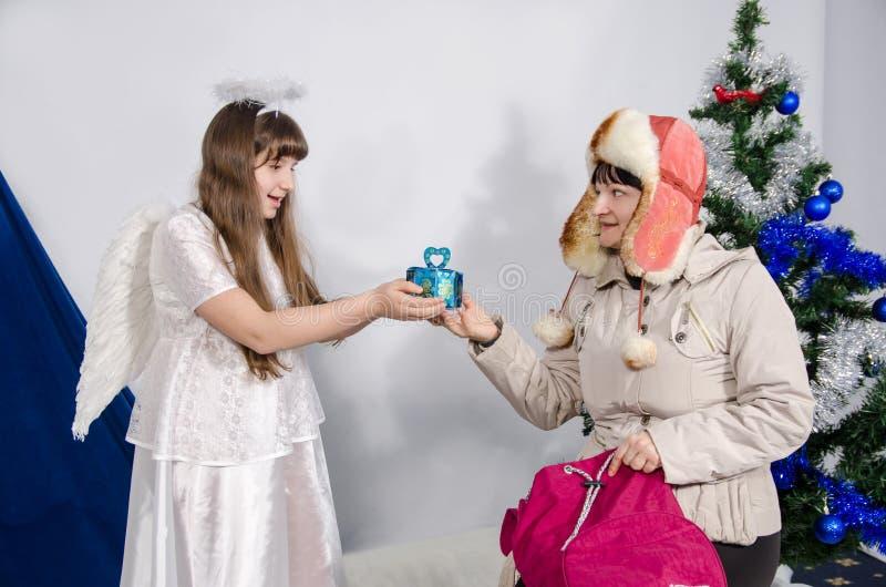 Женщина дает подарок к девушке в костюме ангела стоковая фотография rf