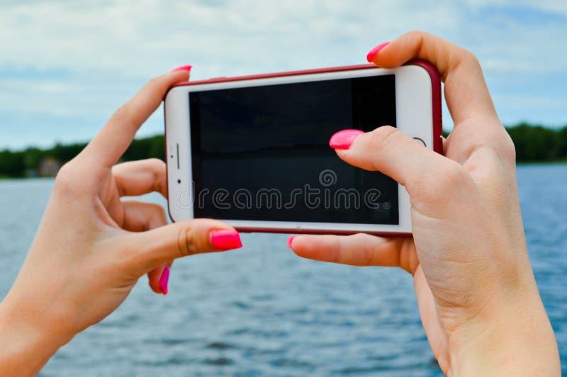 Женщина девушки с красивыми ногтями делает маникюр розовые оранжевые владения в ее руках смартфон мобильного телефона и принимает стоковое изображение rf