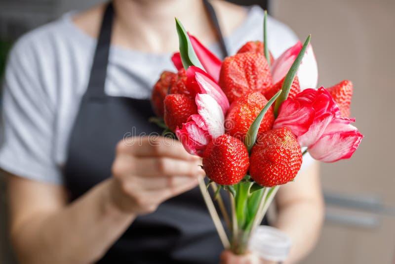 Женщина делает первоначальный букет из красивых тюльпанов и зрелых клубник стоковое фото