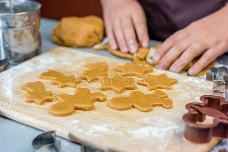 Женщина делает печенья пряника рождества Резцы теста и металла на деревянном столе, горизонтальном стоковая фотография rf