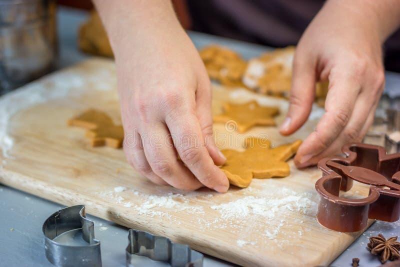 Женщина делает печенья пряника рождества Резцы теста и металла на деревянном столе, горизонтальном стоковые фотографии rf