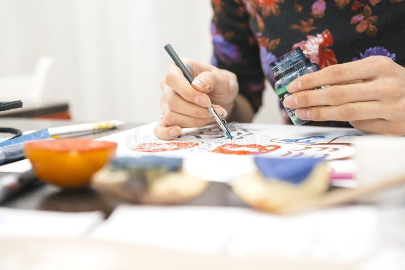 Женщина делает сочинительства каллиграфии, делает искусство на бумаге используя ручку b стоковое изображение rf