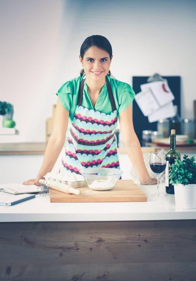 Женщина делает торты в кухне стоковое изображение
