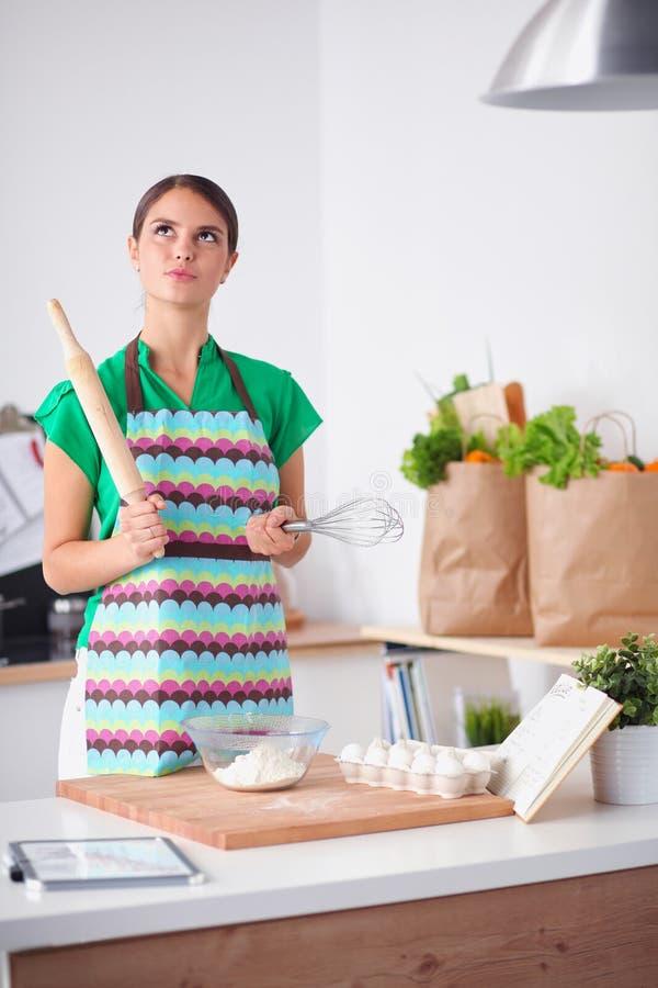 Женщина делает торты в кухне стоковая фотография rf