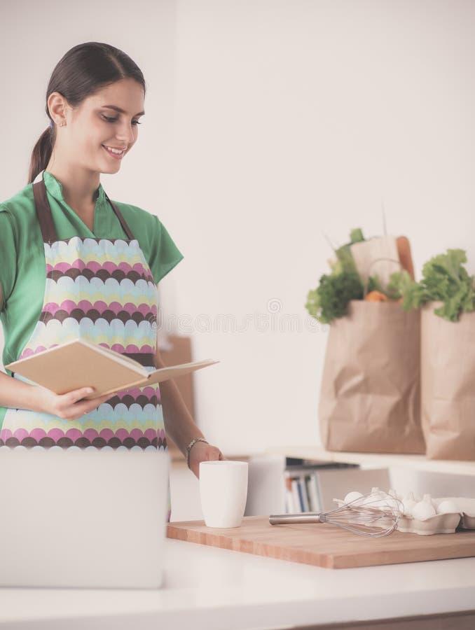 Женщина делает торты в кухне стоковые изображения