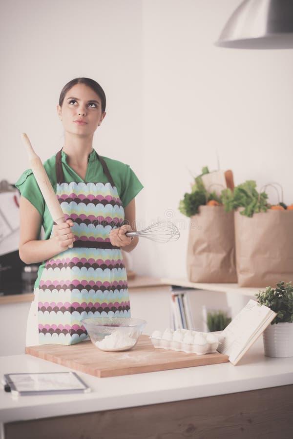 Женщина делает торты в кухне стоковая фотография