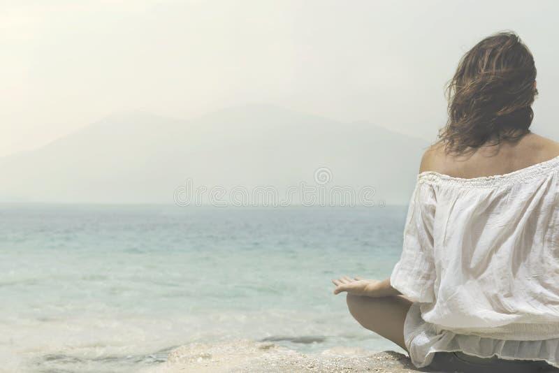 Женщина делает тренировки йоги перед океаном стоковые фотографии rf