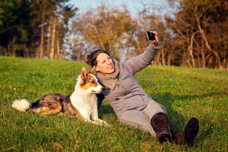 Женщина делает selfie с ее собакой на зеленом луге стоковые фотографии rf
