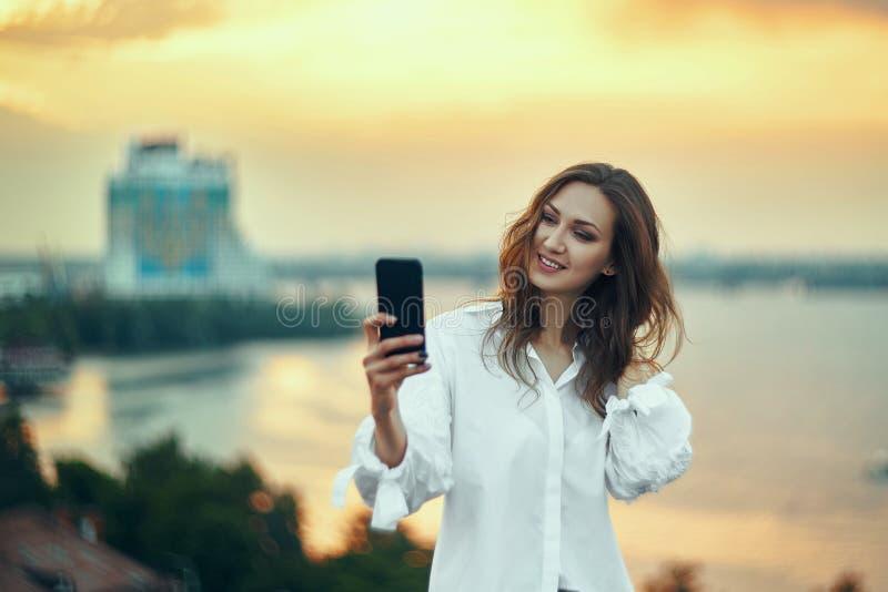 Женщина делая автопортрет с ее умным телефоном над заходом солнца городского пейзажа золотым стоковые фотографии rf