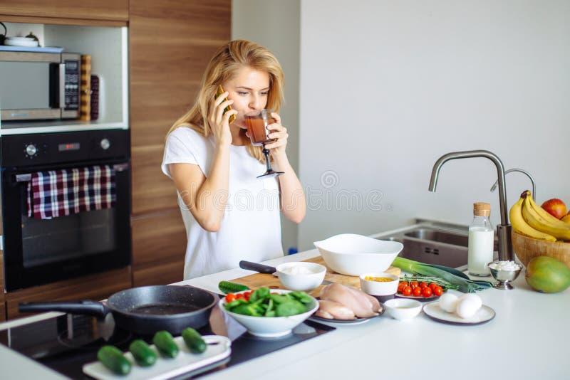 Женщина делая здоровую еду и читая сообщение на телефоне в отечественной кухне стоковые изображения rf