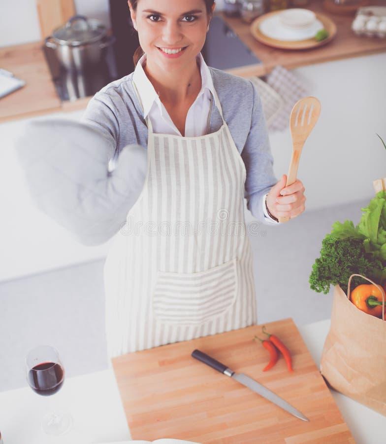Женщина делая здоровую еду стоя усмехающся в кухне стоковое фото rf