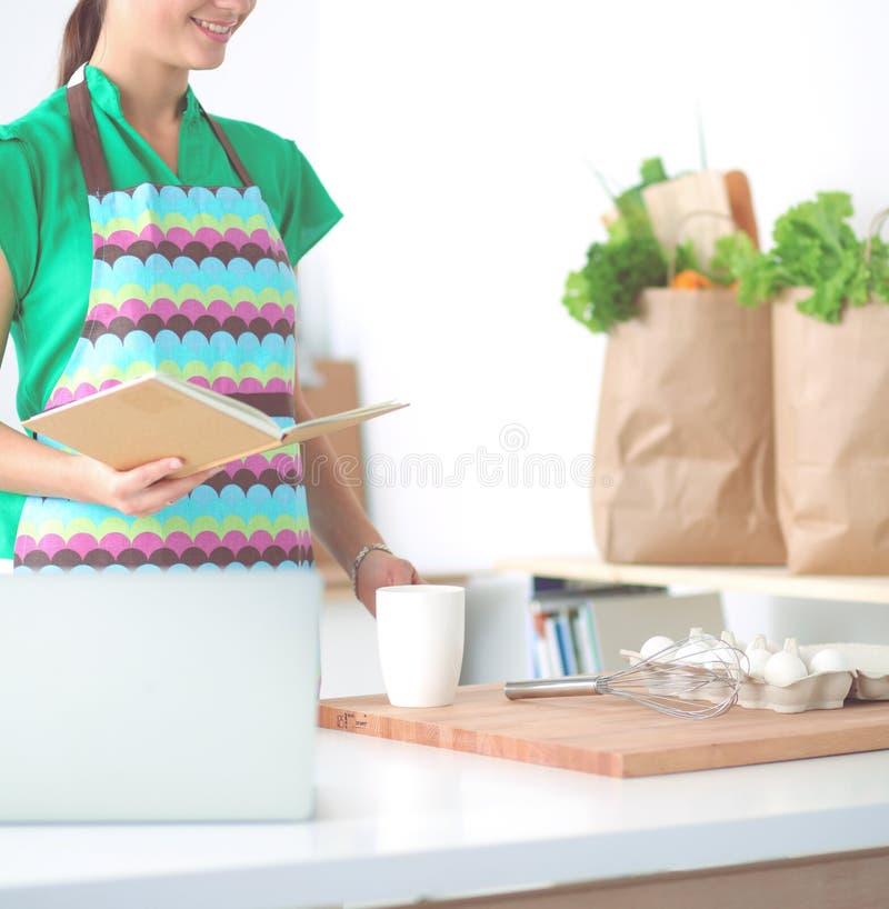 Женщина делая здоровую еду стоя усмехающся в кухне стоковая фотография rf