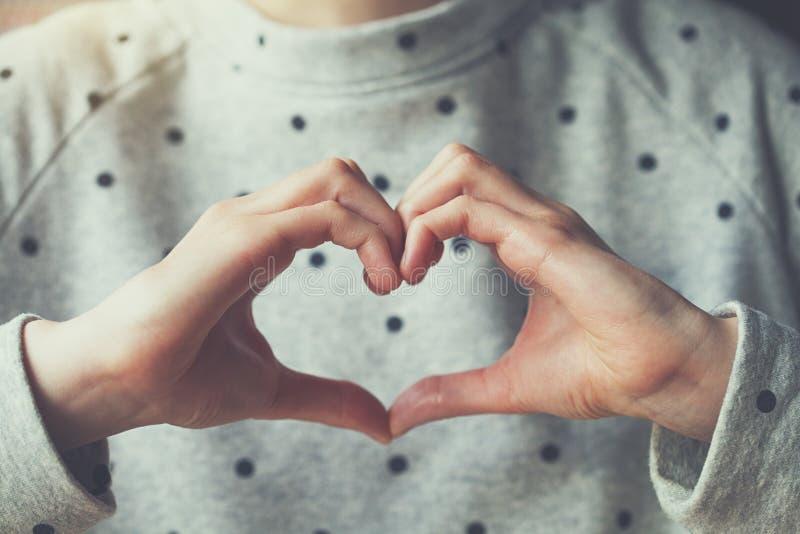 женщина делая знак формы сердца с ее руками стоковое изображение rf