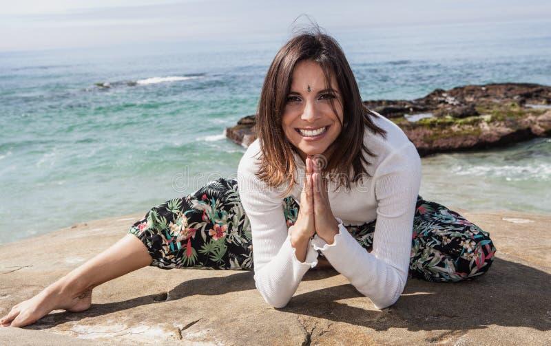 Женщина делая йогу океаном стоковые фото