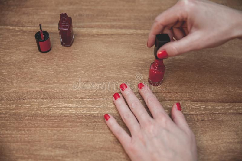 Женщина делая маникюр прикладывая красный маникюр на деревянном столе стоковые фотографии rf