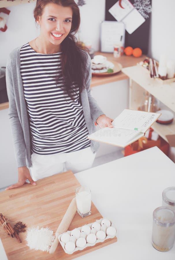 Женщина делая печенья рождества в кухне стоковые фото