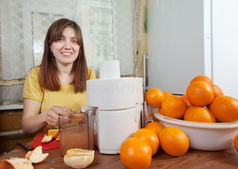 Женщина делая свежий апельсиновый сок стоковая фотография rf