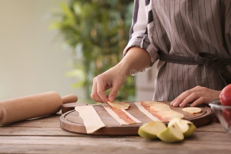 Женщина делая торты яблока в кухне стоковое фото rf