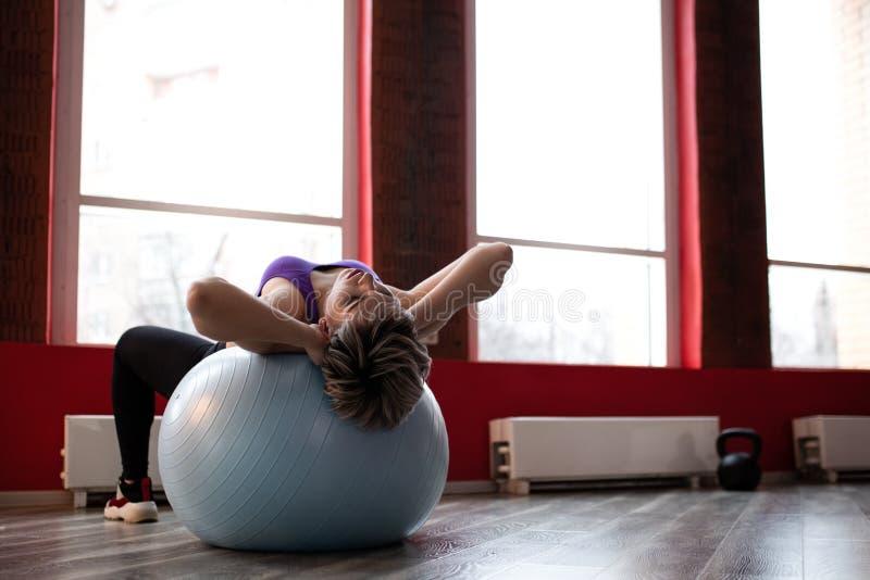 Женщина делая тренировки с fitball в тренажерном зале фитнеса Включая мышцы ядра подбрюшные Концепция изображения здорового стоковое фото