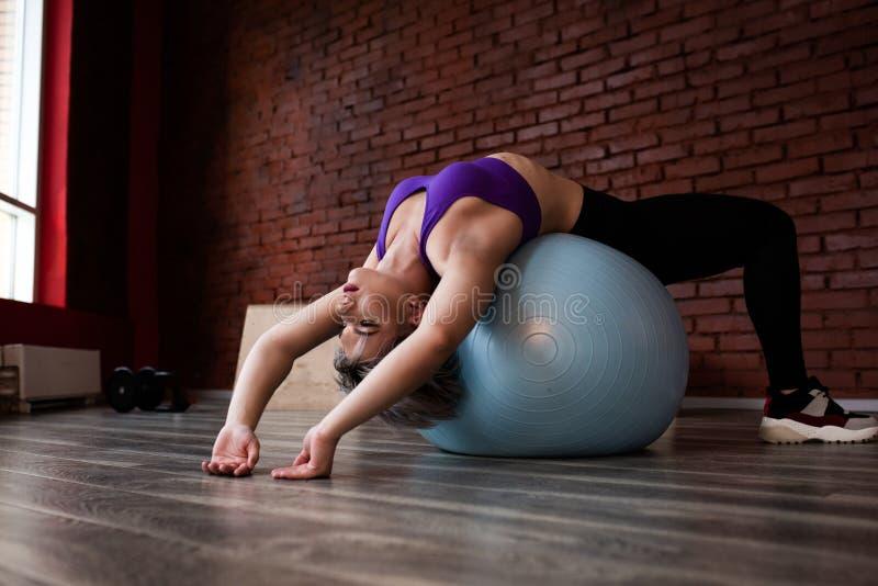 Женщина делая тренировки с fitball в тренажерном зале фитнеса Включая мышцы ядра подбрюшные Концепция изображения здорового стоковое изображение