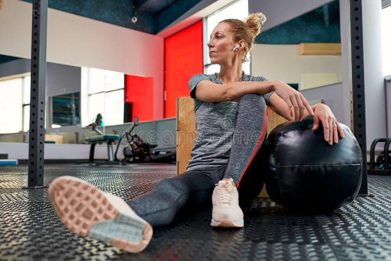 Женщина делая тренировки с fitball в тренажерном зале фитнеса Включая мышцы ядра подбрюшные Концепция изображения здорового стоковое фото rf