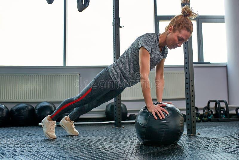 Женщина делая тренировки с fitball в тренажерном зале фитнеса Включая мышцы ядра подбрюшные Концепция изображения здорового стоковые изображения