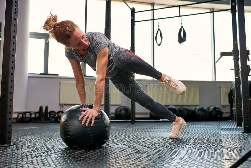 Женщина делая тренировки с fitball в тренажерном зале фитнеса Включая мышцы ядра подбрюшные Концепция изображения здорового стоковые фотографии rf