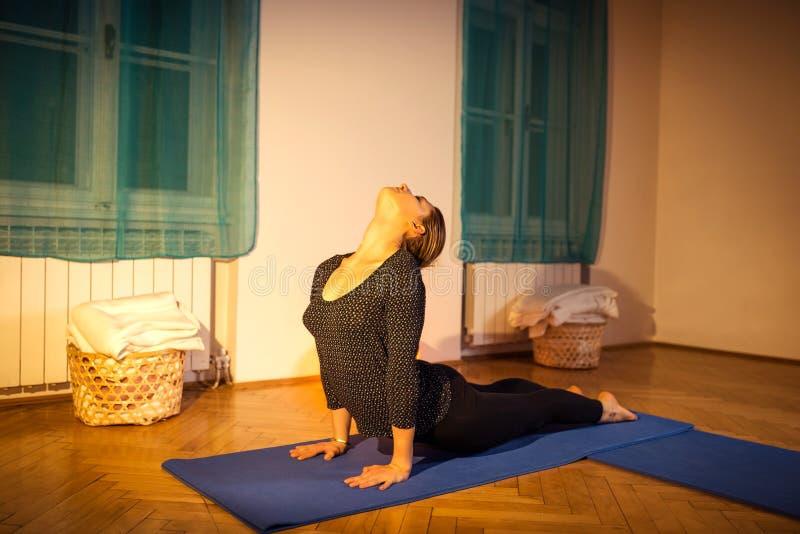 Женщина делая тренировку йоги asana кобры стоковая фотография rf