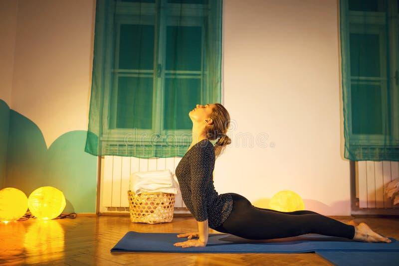 Женщина делая тренировку йоги asana кобры стоковые фотографии rf