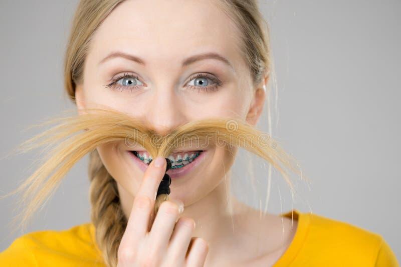 Женщина делая усик из светлых волос стоковые изображения