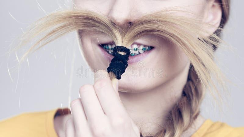 Женщина делая усик из светлых волос стоковое фото
