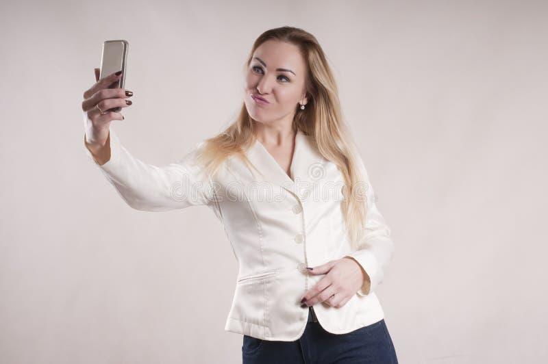 Женщина делая selfie на показе managerstudio smartphone стоковые изображения