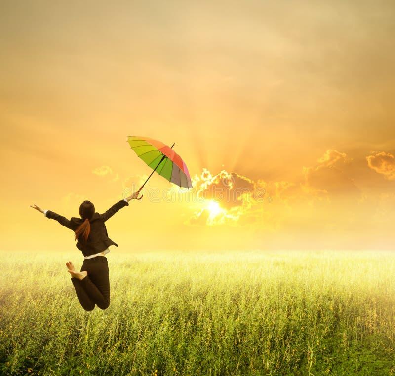 Женщина дела скача к заходу солнца с красным зонтиком стоковая фотография