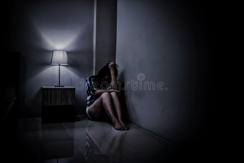 Женщина депрессии самостоятельно в темной комнате Проблема психических здоровий, PTSD стоковые изображения rf