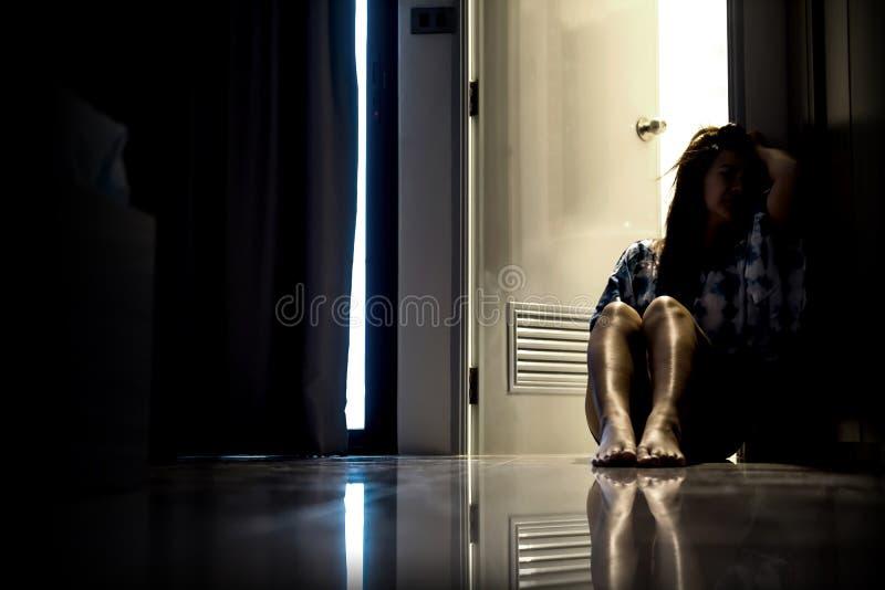 Женщина депрессии самостоятельно в темной комнате Проблема психических здоровий стоковое фото