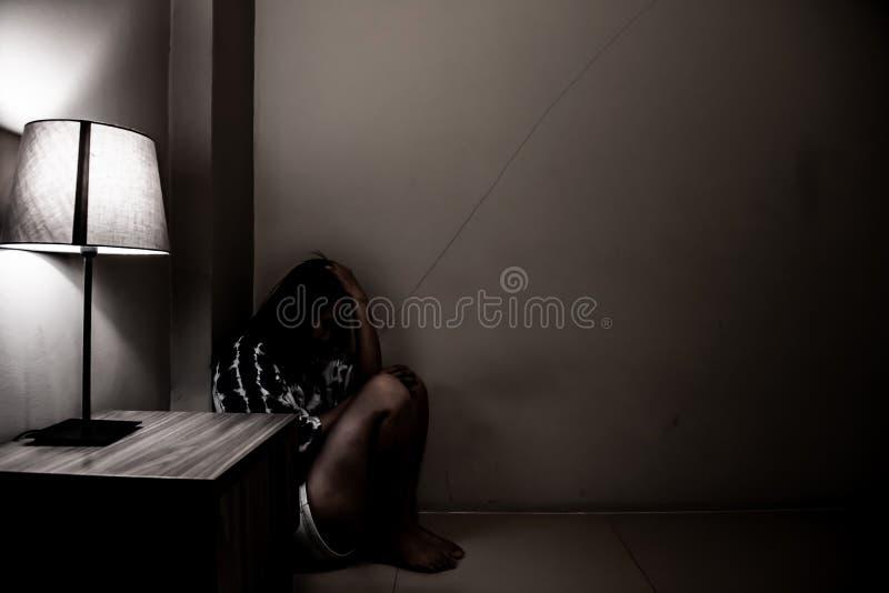 Женщина депрессии самостоятельно в темной комнате Проблема психических здоровий, PTSD стоковое изображение rf