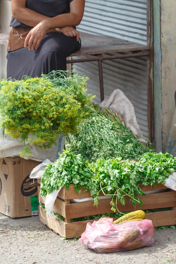 Женщина деревни продавая уличный рынок parsey и овощей стоковые фото