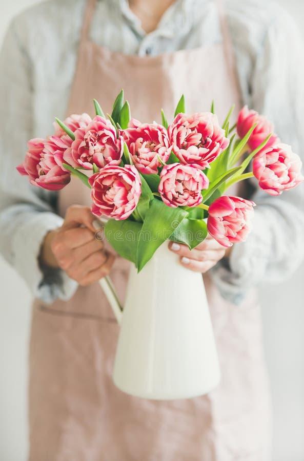 Женщина держа белую вазу эмали с свежими розовыми тюльпанами стоковые фотографии rf
