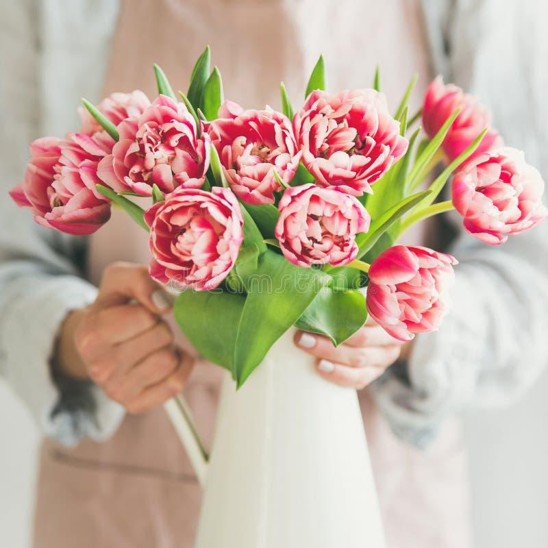 Женщина держа белую вазу эмали с свежими розовыми тюльпанами стоковые изображения