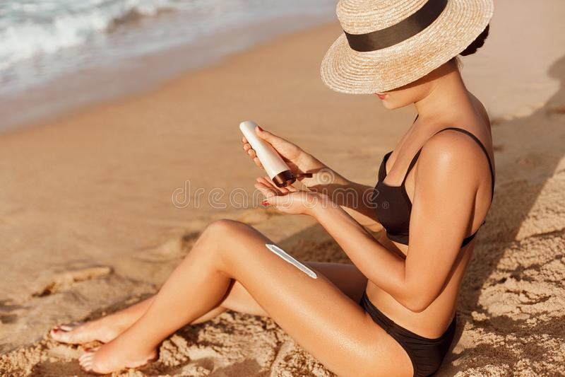 Женщина держа бутылки солнцезащитного крема в ее руках Skincare Сливк солнца предохранения от Солнца, на ее ровных загоренных ног стоковая фотография rf