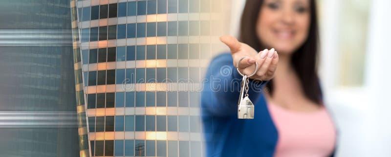 Женщина держа вне ключи дома; множественная выдержка стоковое фото