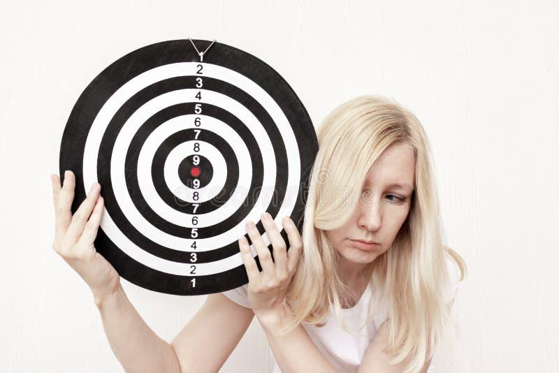 Женщина держа доску дротика в руках близко вверх, направляя и целясь концепцию стоковое фото
