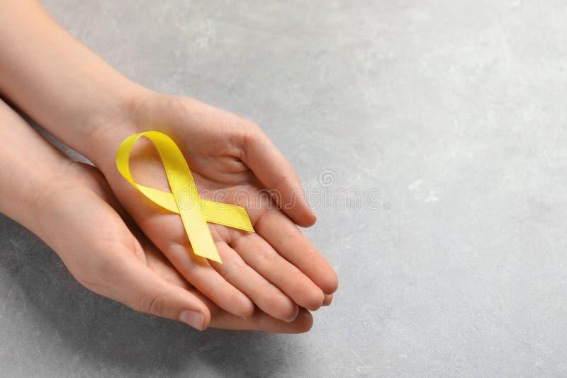 Женщина держа желтую ленту на серой предпосылке стоковое фото