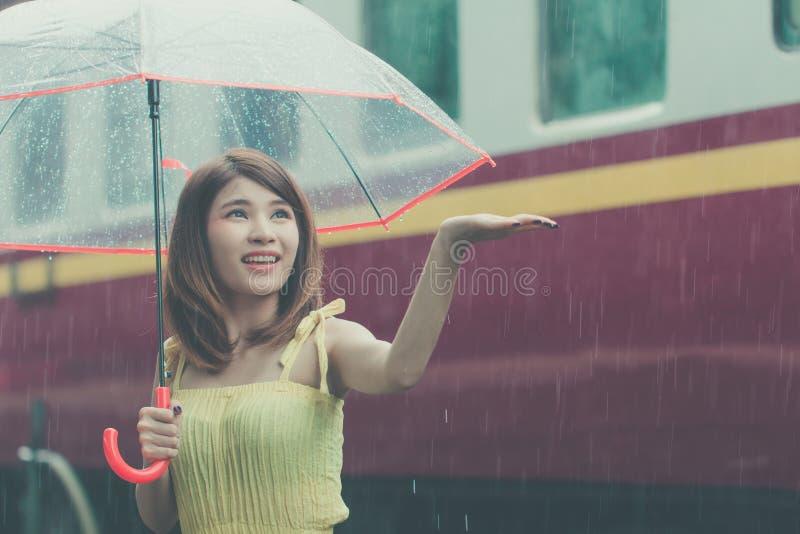 Женщина держа зонтик в дождливом дне Азиатская девушка на весеннем сезоне стоковое фото rf