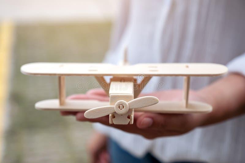 Женщина держа и показывая деревянный самолет в ее руке стоковая фотография rf