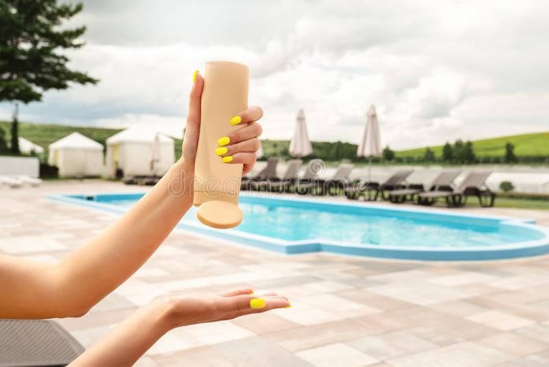 Женщина держа и сжимая УЛЬТРАФИОЛЕТОВОЕ suncream защиты на ее руке на плавательном бассеине гостиницы стоковое изображение