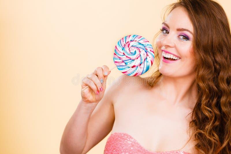 Женщина держа красочную конфету леденца на палочке в руке стоковые изображения rf
