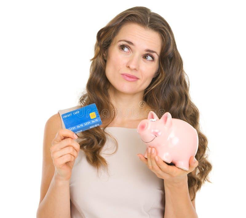Женщина держа кредитную карточку и piggy банк стоковая фотография rf